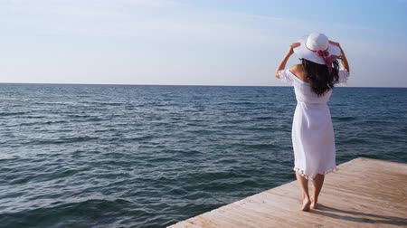 yalınayak : Young woman stands on wooden pier, looking at the sea. Stok Video