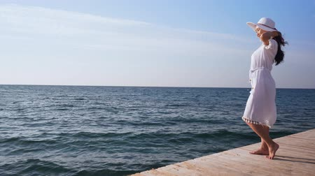 Young woman in white dress stands on wooden pier. Wideo