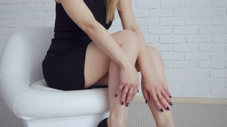 calçados : Sexy woman in black dress sitting in white chair. Stock Footage