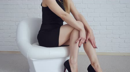 Sexy woman in black dress sitting in white chair. Wideo