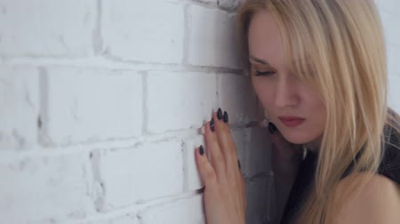 Yound beautiful sad woman posing near white brick wall.