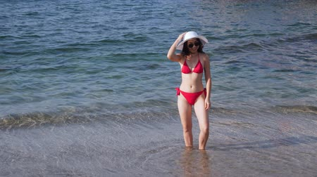 Woman dressed in red swimwear stands in water on beach.