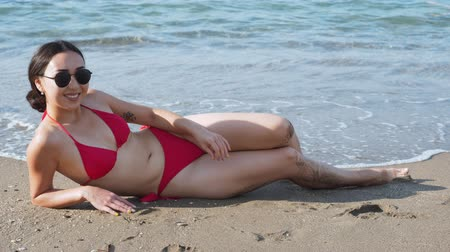 Woman in red swimsuit lying on the beach and sunbathing.
