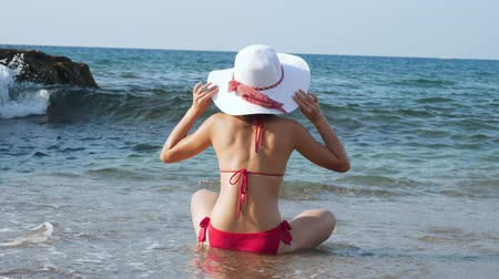 sunhat : Young woman sitting on the beach in front of blue sea.