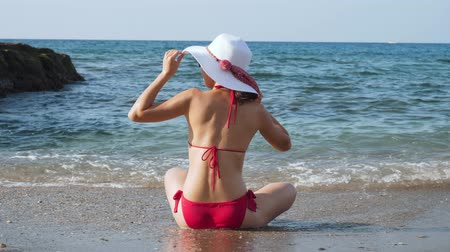 curtimento : Young woman sitting on the beach in front of blue sea.