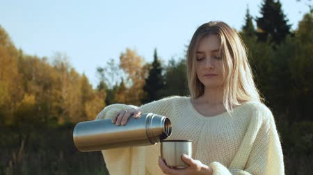flasks : Young woman in pouring hot tea with steam from bottle to mug. Stock Footage