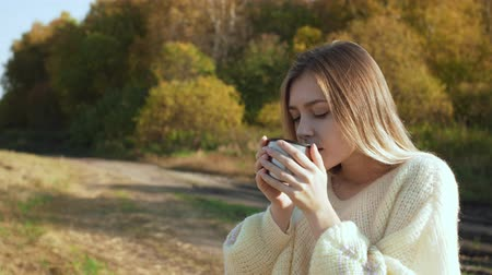 Beautiful admiring woman drinking hot tea from bottle cup Wideo
