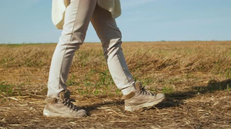 Unrecognizable woman legs walking in autumn field.
