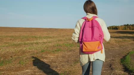 Young woman with pink backpack walking