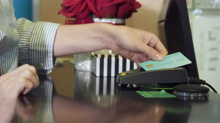 card pin : Woman tapping credit card on payment terminal.