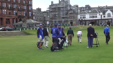 clubhouse : Golfers and caddies meet at the Old Course at St Andrews - These golfers from all over the world took part in a golf course on the Old Course at St Andrews. The Old Course is one of the few golf courses in the world that still has a real caddy program.