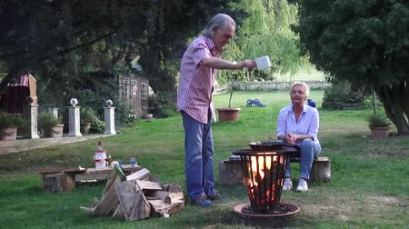repousante : The young woman is preparing for the delicious fried eggs in french style with tarragon and cheese baked, which her husband prepares in a frying pan over the campfire for her