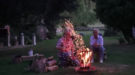 restful : For the romantic campfire, the man sorts the wood in the fire basket, the flames and sparks illuminate the scene