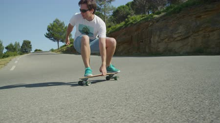 longboarder : SLOW MOTION: Young man longboarding down the winding road