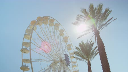 пальмовые деревья : SLOW MOTION: Ferris wheel spinning slowly on a sunny day