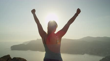 sucesso : SLOW MOTION CLOSE UP: Young happy woman reaches top of the mountain cliff and raises her arms successfully against the beautiful sunset sky