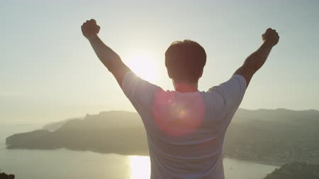braços levantados : SLOW MOTION CLOSE UP: Cheerful young man raising his hands high on top of the big mountain above the ocean at beautiful golden sunset