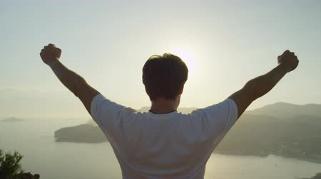 braços levantados : SLOW MOTION CLOSE UP: Successful young man with arms raised high standing on top of the ocean cliff above the city at beautiful golden sunset, sun shining through the hands