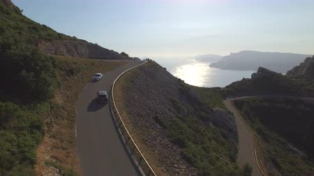 passar : AERIAL: Car driving up the mountain pass above the ocean at beautiful summer sunset