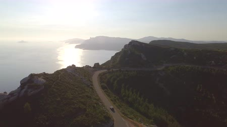 passar : AERIAL: SUV jeep driving along the road on top of high cliffs above the ocean in beautiful sunny summer