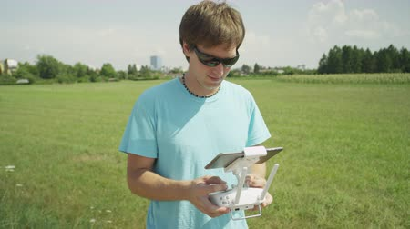 emisor : SLOW MOTION: Cheerful young pilot flying the RC drone Archivo de Video