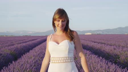 valensole : SLOW MOTION: Happy young woman in beautiful endless lavender field