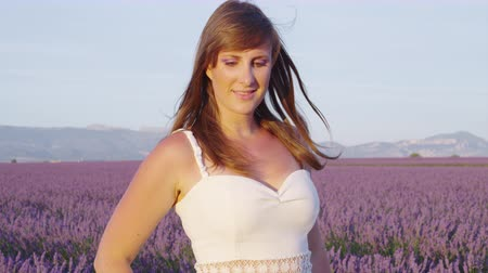 valensole : SLOW MOTION CLOSE UP: Young lady in white dress walking through beautiful purple lavender field