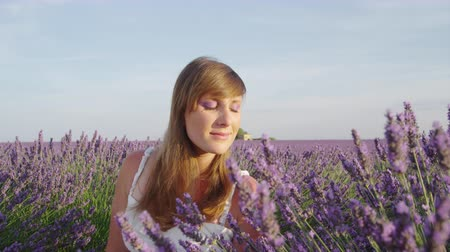 valensole : SLOW MOTION CLOSE UP: Woman smelling scented flowers in beautiful lavender field