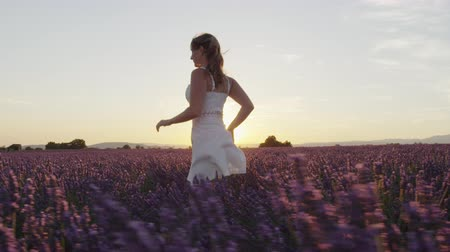 valensole : SLOW MOTION: Cheerful young woman in white dress running through beautiful purple lavender field at golden sunset in summer Stock Footage
