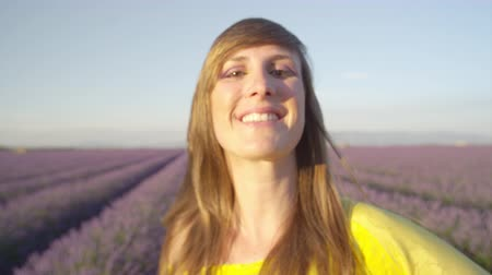 valensole : CLOSE UP: Young woman smiling into camera in beautiful purple lavender field in summer evening