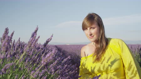 valensole : SLOW MOTION CLOSE UP: Woman in long yellow dress walking through beautiful purple lavender field