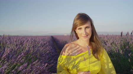 smell : SLOW MOTION CLOSE UP: Happy young woman smelling scented lavender and smiling into camera