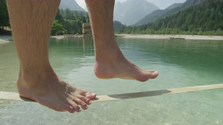 slacklining : SLOW MOTION CLOSE UP: Man walking on slackline over the beautiful mountain lake on a sunny day in summer