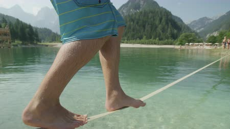 slacklining : SLOW MOTION CLOSE UP: Young man slacklining and balancing above the beautiful mountain lake and falling into the water