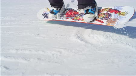 ski boots : SLOW MOTION CLOSE UP: Snowboarder riding and falling on ski slope in sunny ski resort