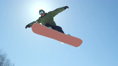 grabbing : SLOW MOTION CLOSE UP: Snowboarder jumping over the sun in snowpark on a beautiful sunny day in snowy ski resort