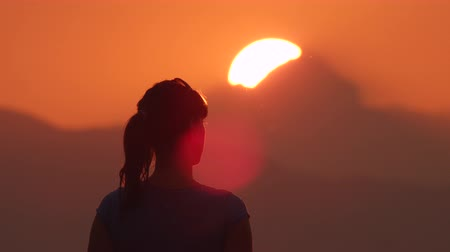 setting : Young woman makes hearts with her hands over the beautiful golden sun setting behind the mountains
