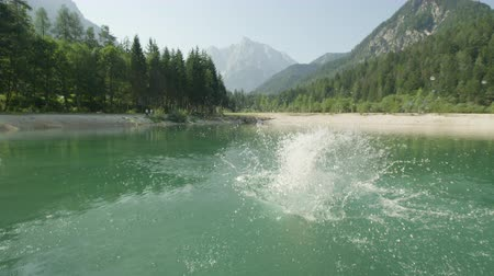 plunging : SLOW MOTION CLOSE UP: Young caucasion woman jumping and diving into crystal clear mountain lake on a beautiful sunny day in summer Stock Footage