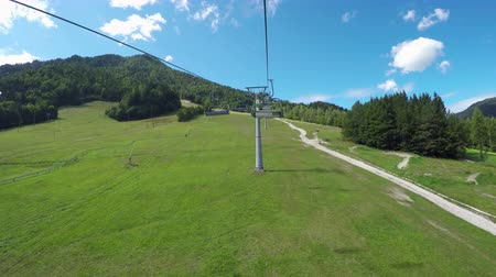 toboggan : FPV: Chairlift ride in sunny mountain resort in sunny summer