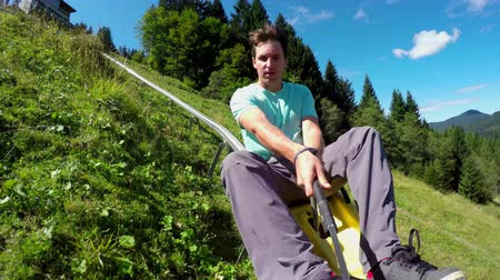 toboggan : SELFIE: Cheerful young man riding summer sledge rollercoaster
