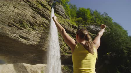 kabarık : SLOW MOTION CLOSEUP: Young woman raising hands in front of the waterfall in beautiful sunny summer Stok Video