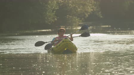 kenu : SLOW MOTION: Happy smiling couple talking and kayaking along the river at beautiful summer sunset Stock mozgókép