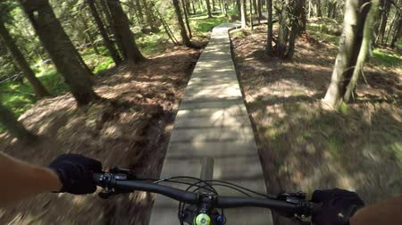 FIRST PERSON VIEW POV: Extreme downhill biker riding on wooden bike trail track
