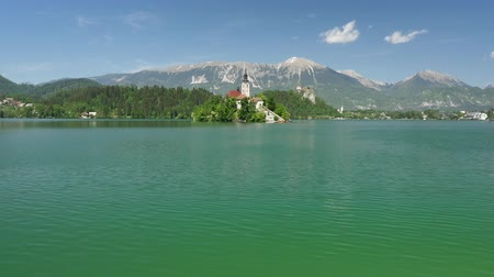 AERIAL: Flying over the lake towards beautiful Bled island church