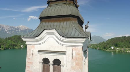 AERIAL CLOSEUP: Bled church landmark with beautiful tall tower and cross in the middle of Bled lake