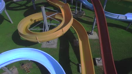 AERIAL: Flying up the toboggan water slides in sunny summer Wideo