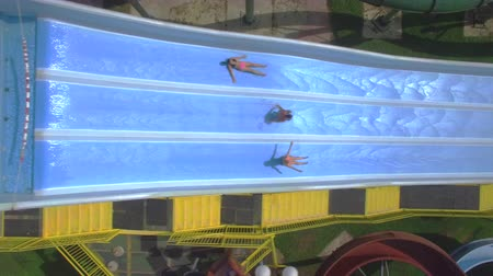AERIAL: Flying above young friends sliding down the fast water slide in summer aqua park Wideo