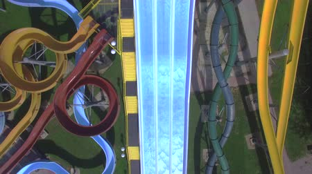 waterslide : AERIAL: Flying above big extreme water park full of toboggans and slides