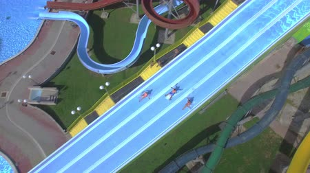 waterslide : AERIAL: Young people having fun in extreme water park on their holidays in sunny summer