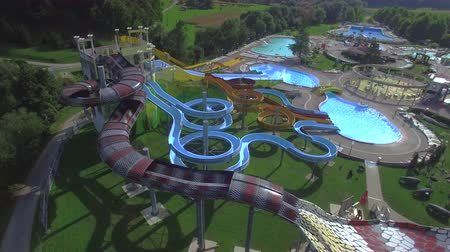 toboggan : AERIAL: Flying around big extreme water park with waterslides toboggans and pools